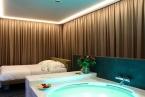 La camera da letto con vasca idromassaggio con tende chiuse.