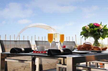 la zona pranzo con mobili Ninix, sullo sfondo la spiaggia con l'amaca Surf