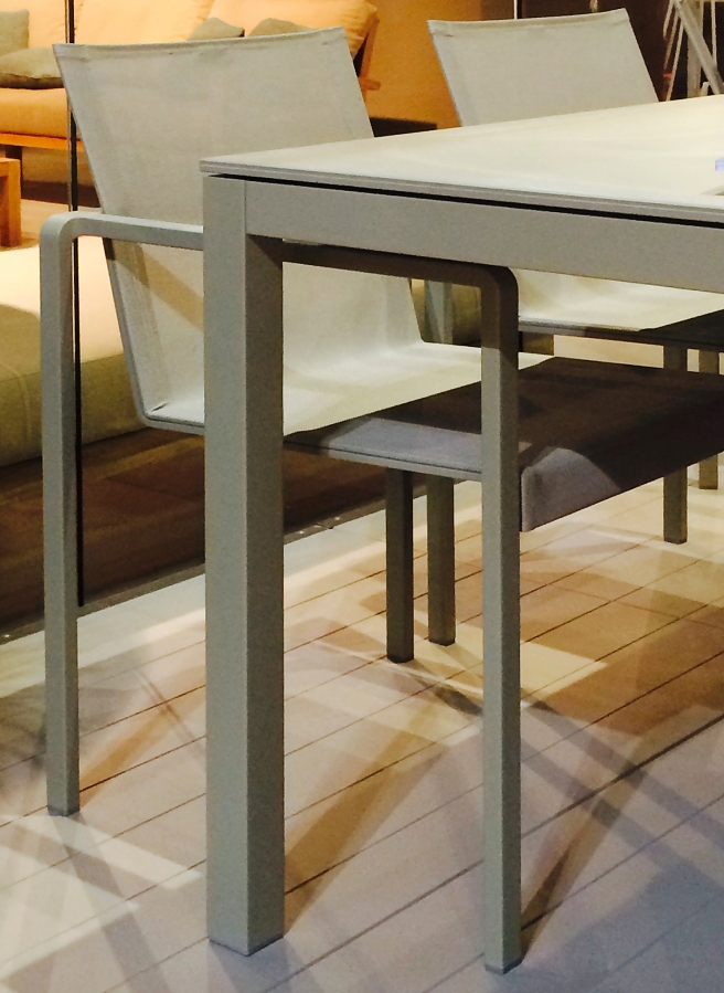 Abbinamento raffinatissimo ton sur ton del tavolo TABOELA con struttura in acciaio verniciato e piano in ceramica, e sedia ALURA con struttura in alluminio verniciato e tessuto Batyline.